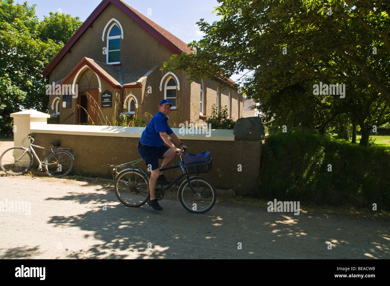 dh  SARK SARK ISLAND Local postman delivering post by bicycle - Stock Image