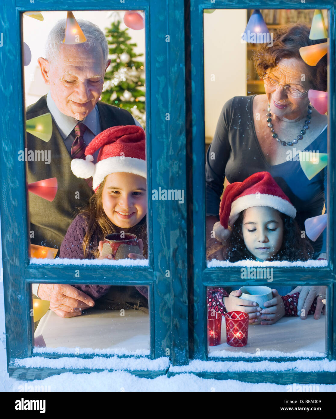 Grandparents and granddaughter at the window on Christmas eve. - Stock Image
