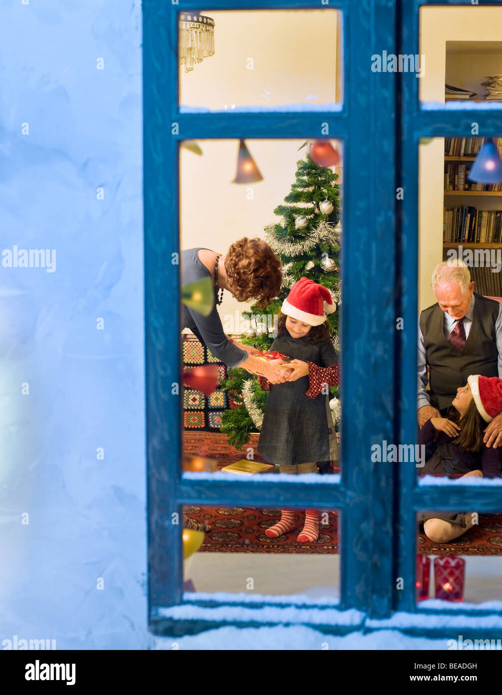 grandparents giving Christmas present to their little granddaughters - Stock Image