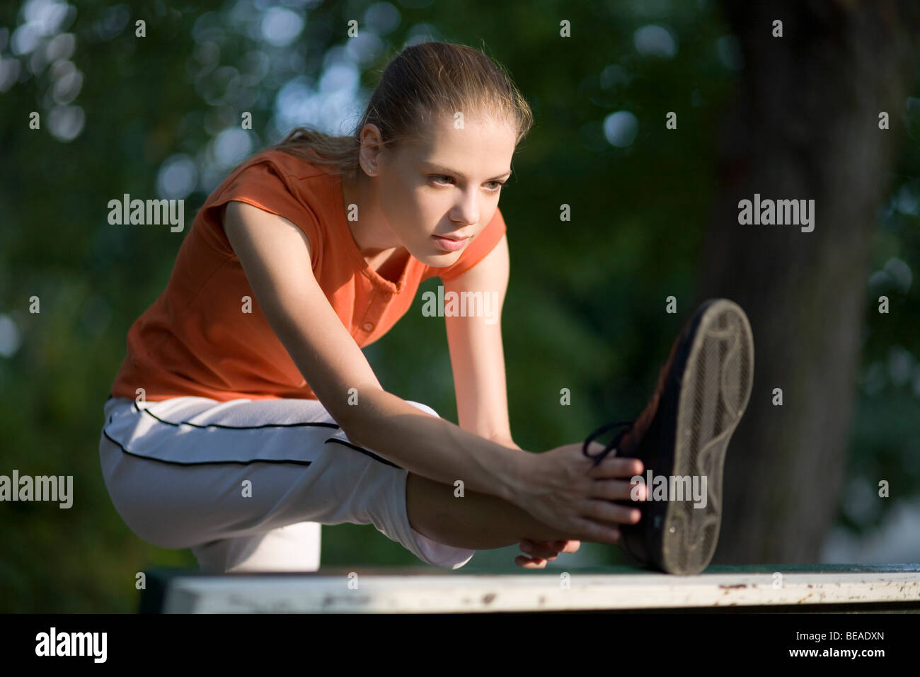 Young woman exercising, stretching in park. - Stock Image
