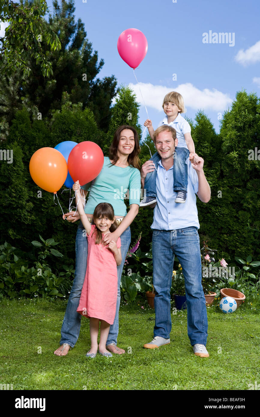 Two parents and their two children holding balloons, outdoors - Stock Image