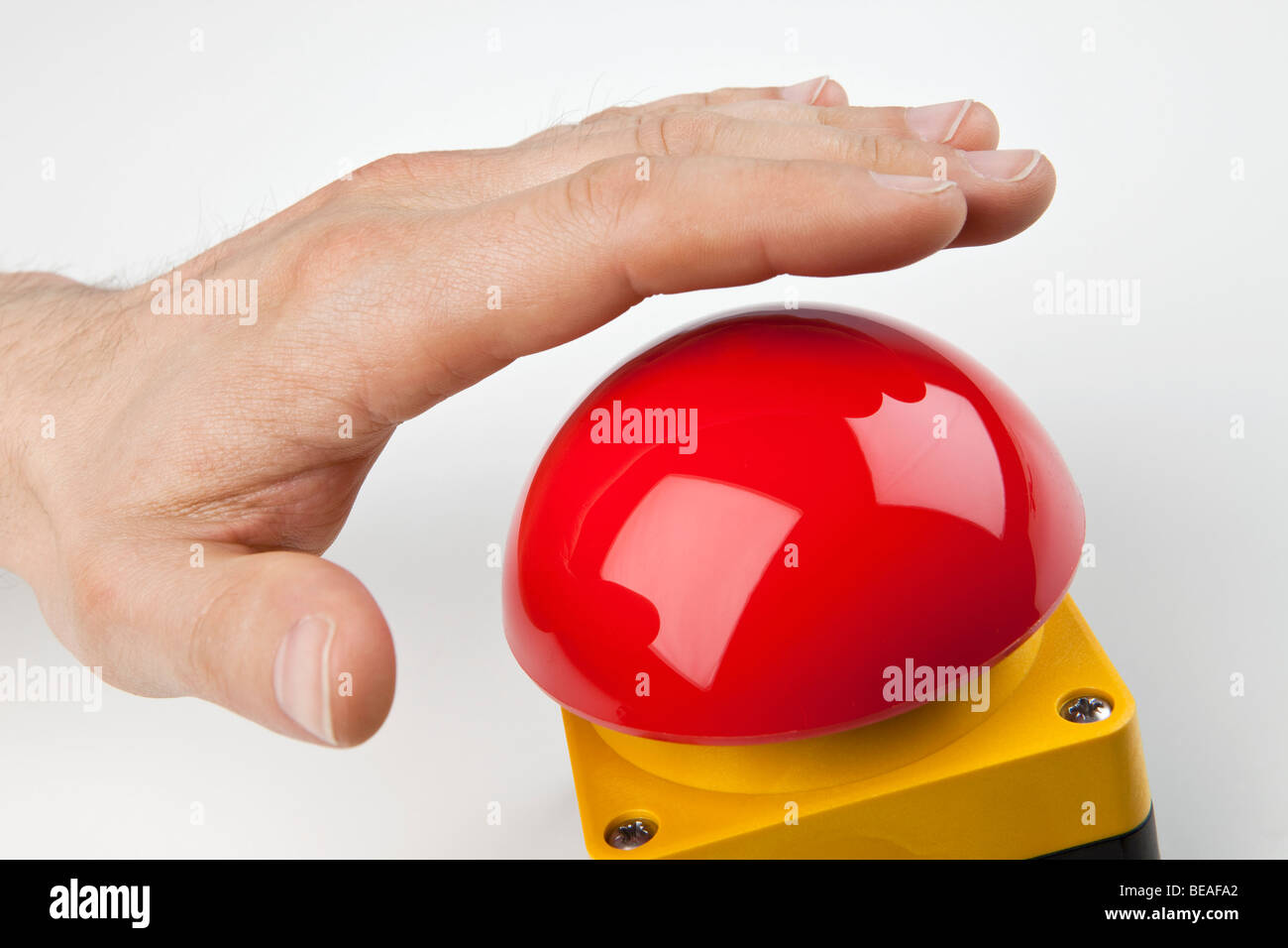 A hand about to press a big red buzzer - Stock Image