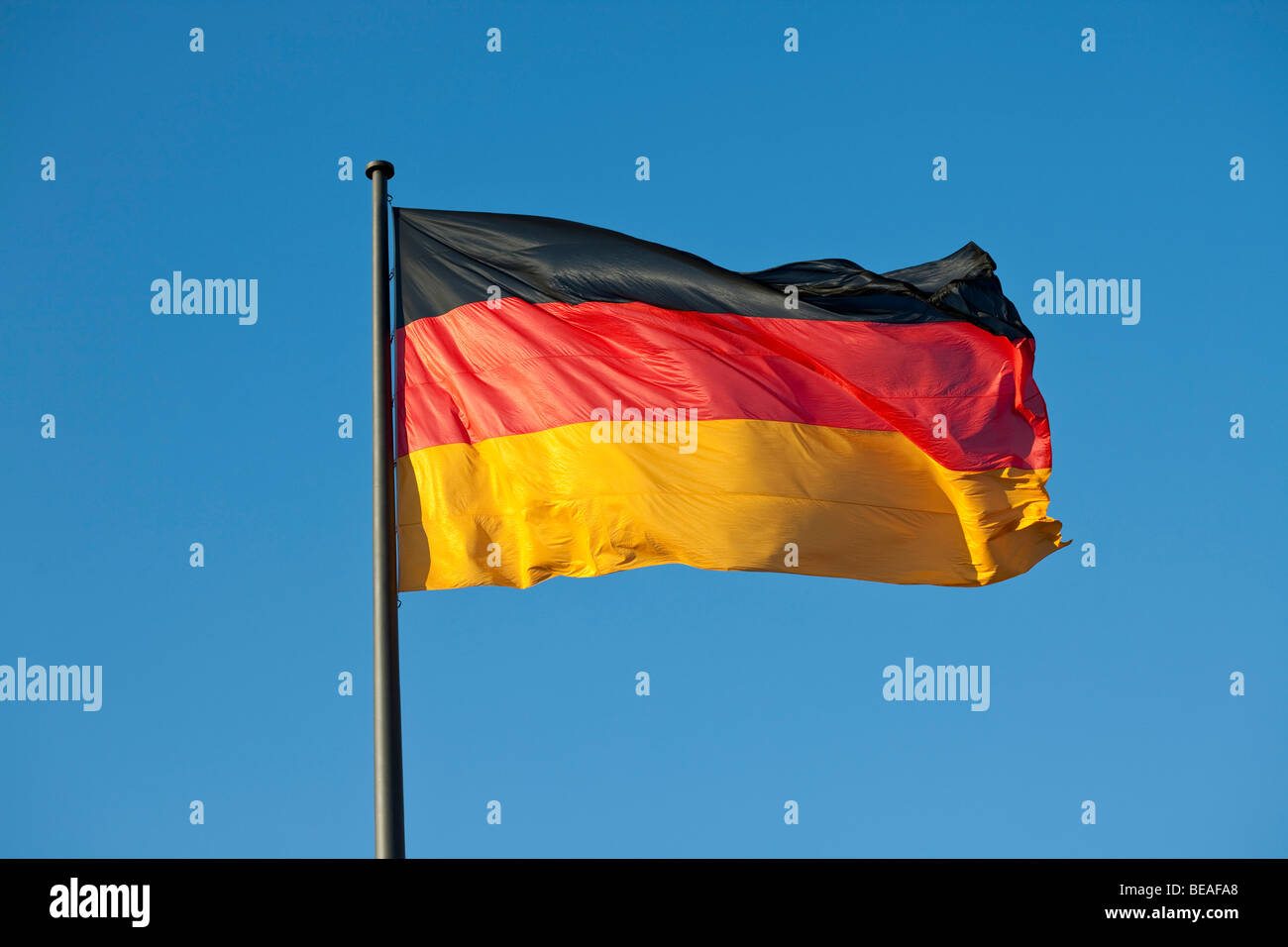 A German flag on a flag pole - Stock Image