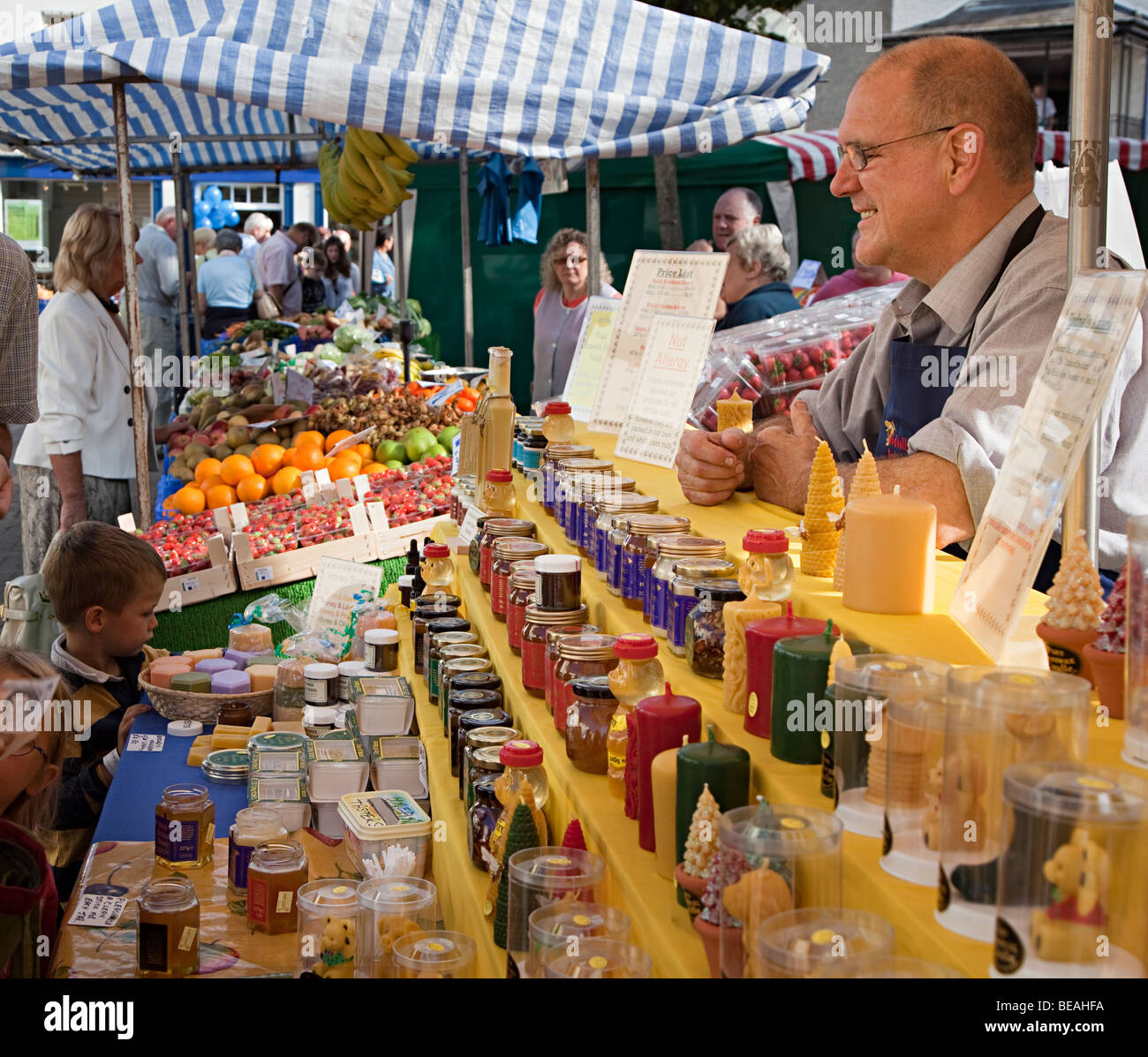 Man selling honey and beeswax products on market stall Abergavenny food festival Wales UK - Stock Image