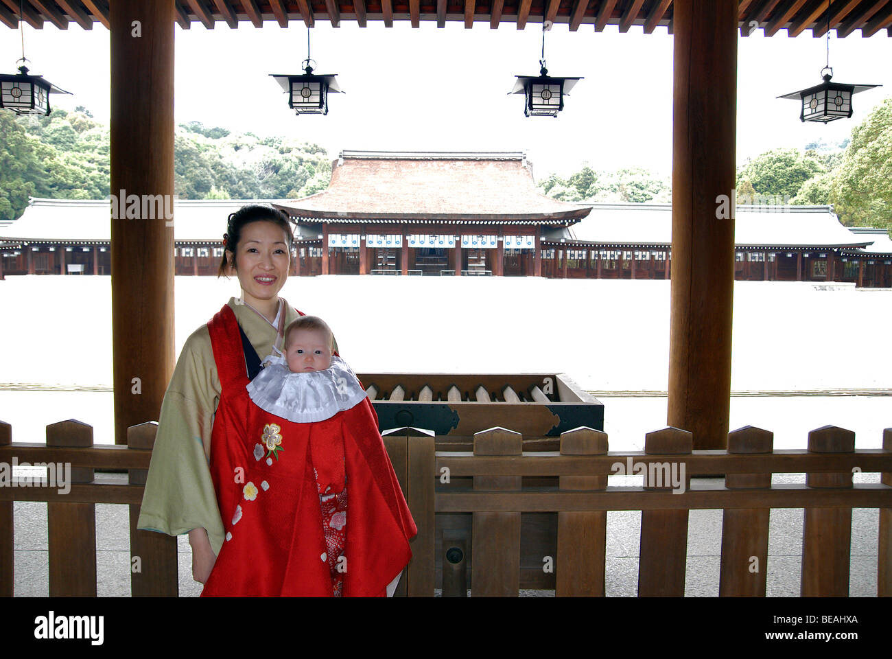 Japanese woman carrying her baby to temple wrapped in a red kimono for a ceremony. Kashihara Shrine, Nara prefecture, - Stock Image
