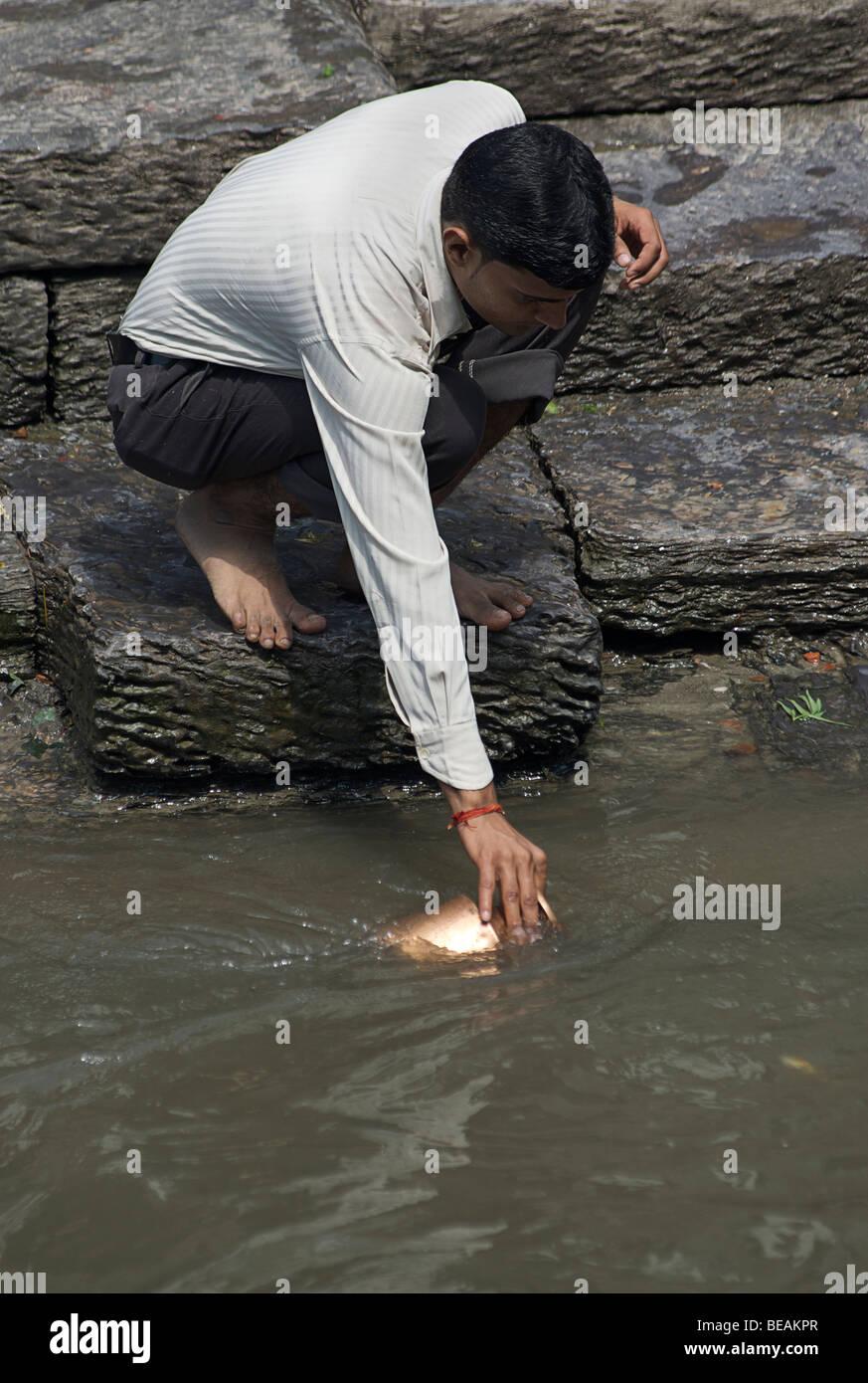Hindu man collecting water for ritual from the Bagmati river at Pashupatinath, Kathmandu, Nepal. - Stock Image