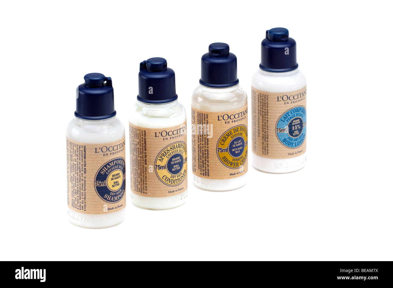 Four plastic bottles of one of each L'Occitane  Shampoo,conditioner,body lotion and shower cream - Stock Image
