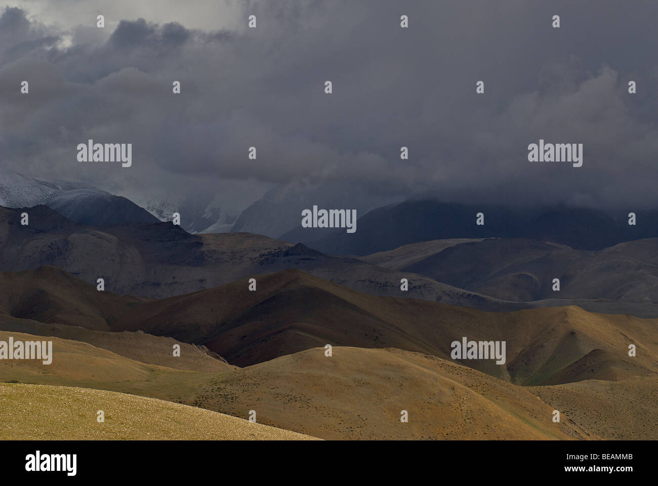 Stormclouds over the plateau. Tibetan landscape with hills and mountains . Approaching Nepal. Tibet, China - Stock Image