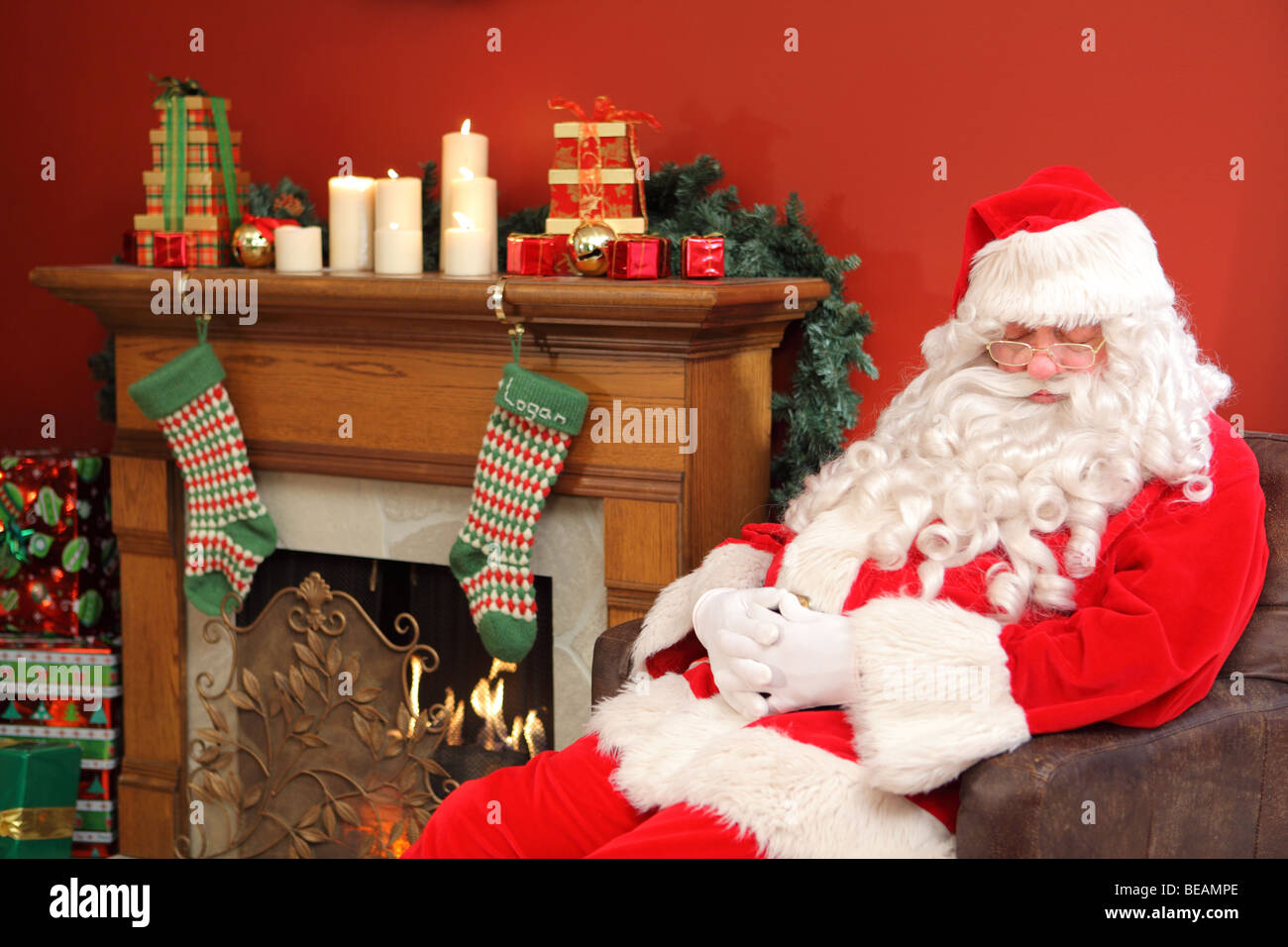 Santa Claus sleeping in chair - Stock Image