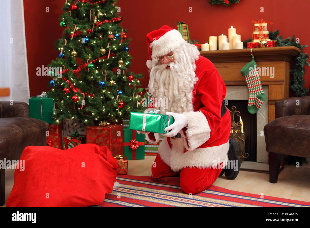 santa claus putting gifts under christmas tree stock image