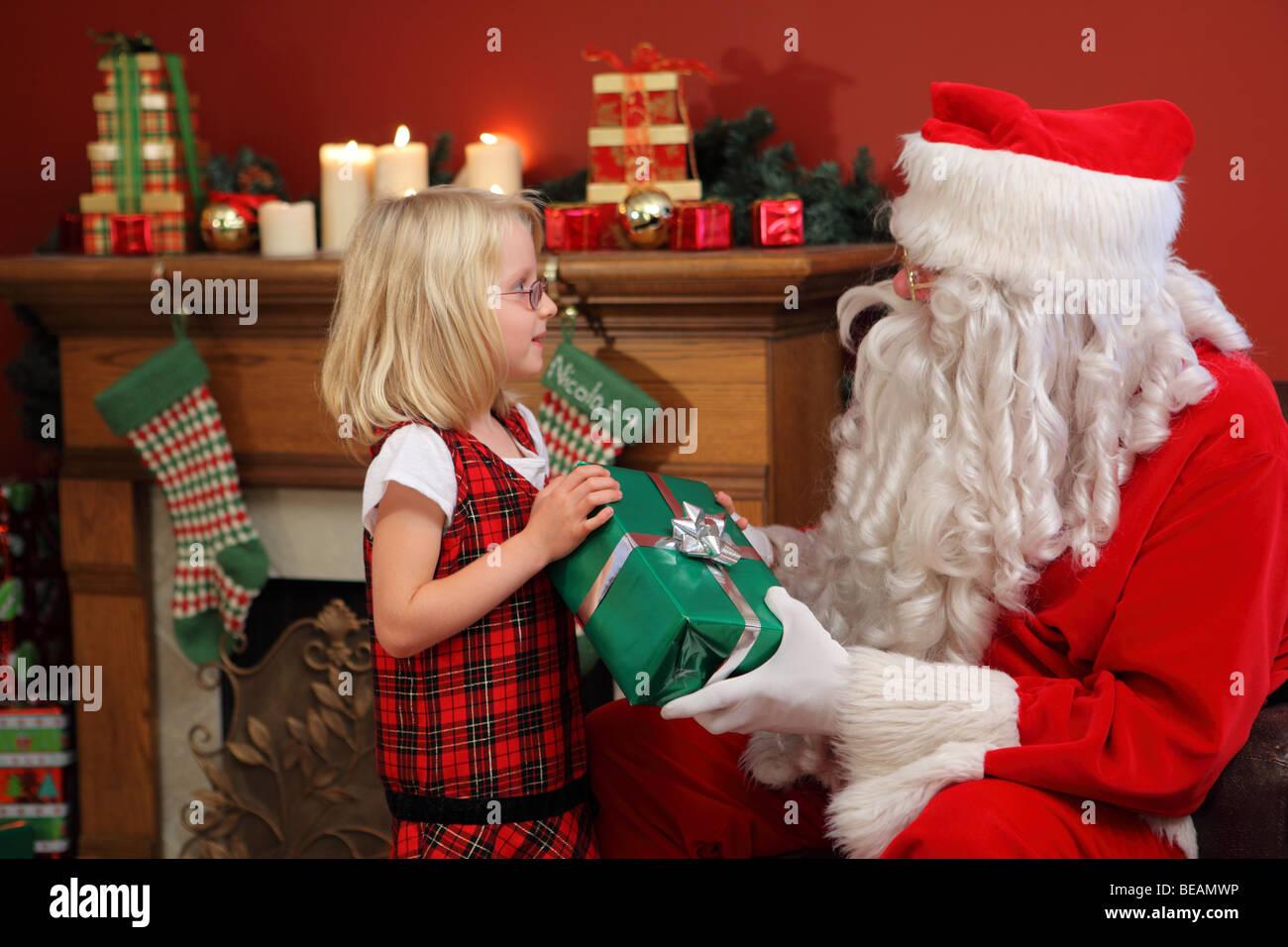 Santa Claus gives young girl Christmas gift - Stock Image