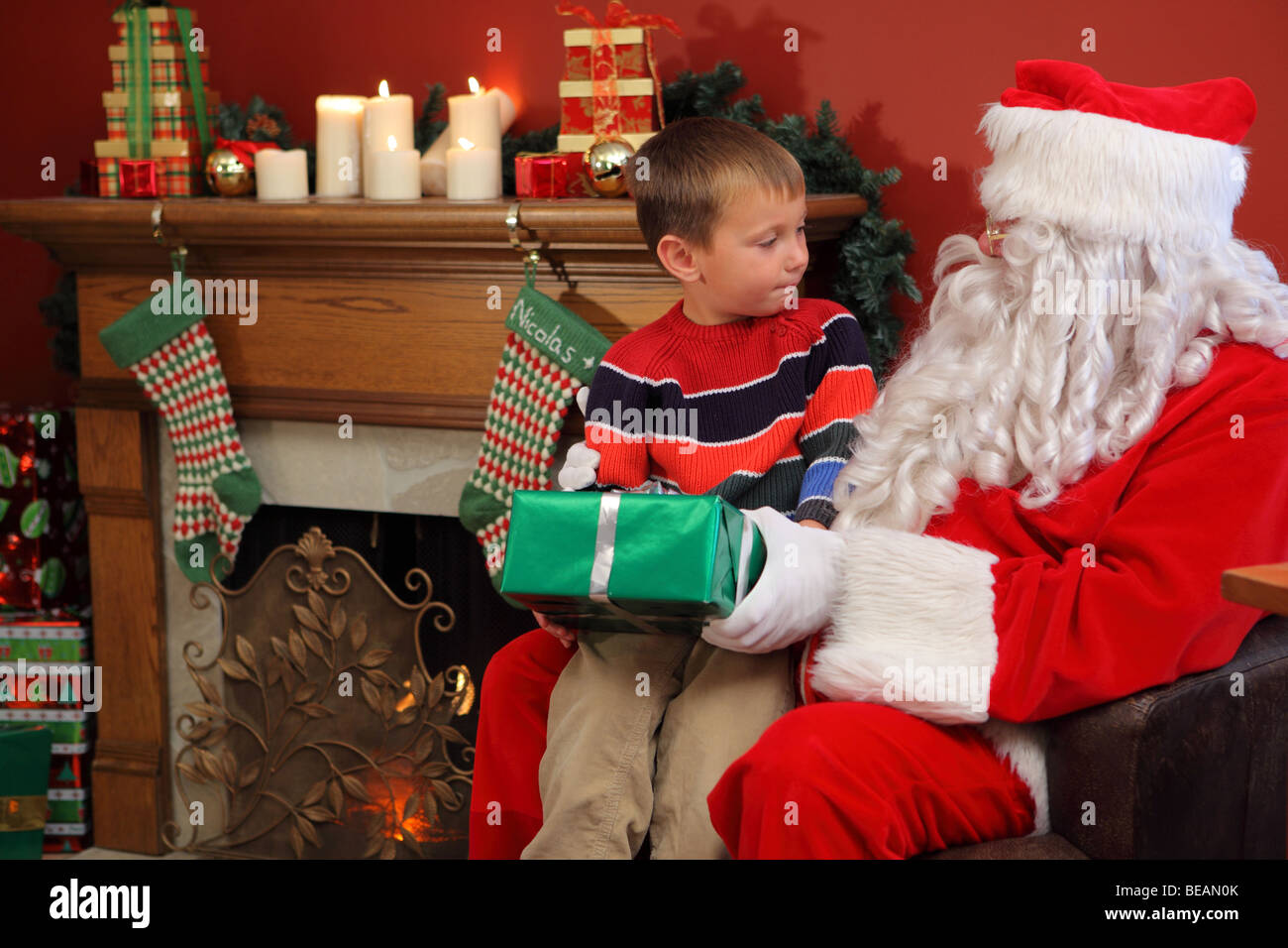 Santa Claus gives young boy Christmas gift - Stock Image