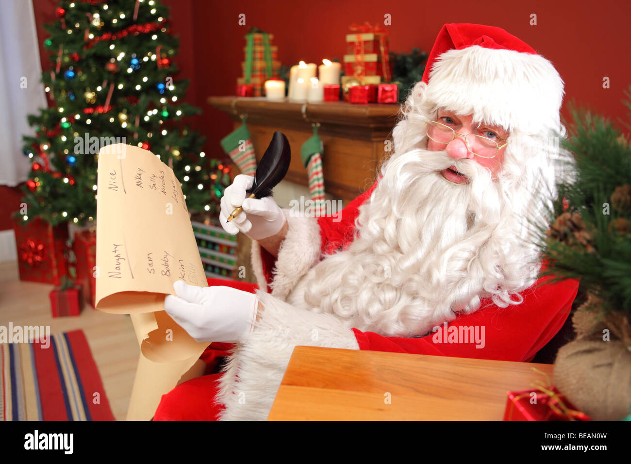 Santa Claus writing names on list - Stock Image