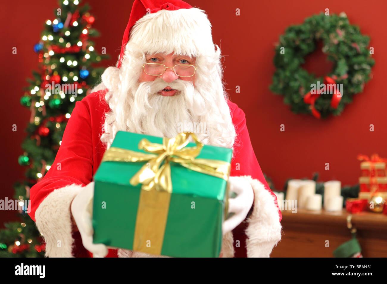 Santa Claus giving gift - Stock Image