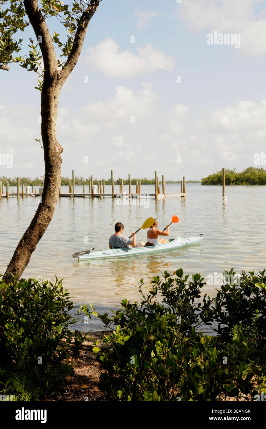 Kayakers in a double kayak paddle between islands in Pine Island Sound, Florida. - Stock Image