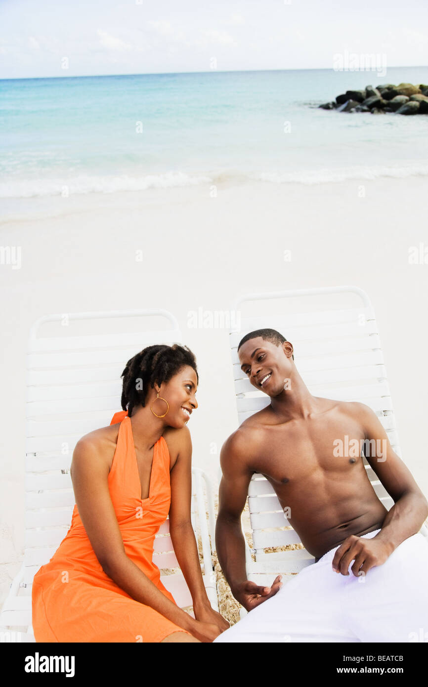 African couple sitting in lounge chairs on beach Stock Photo