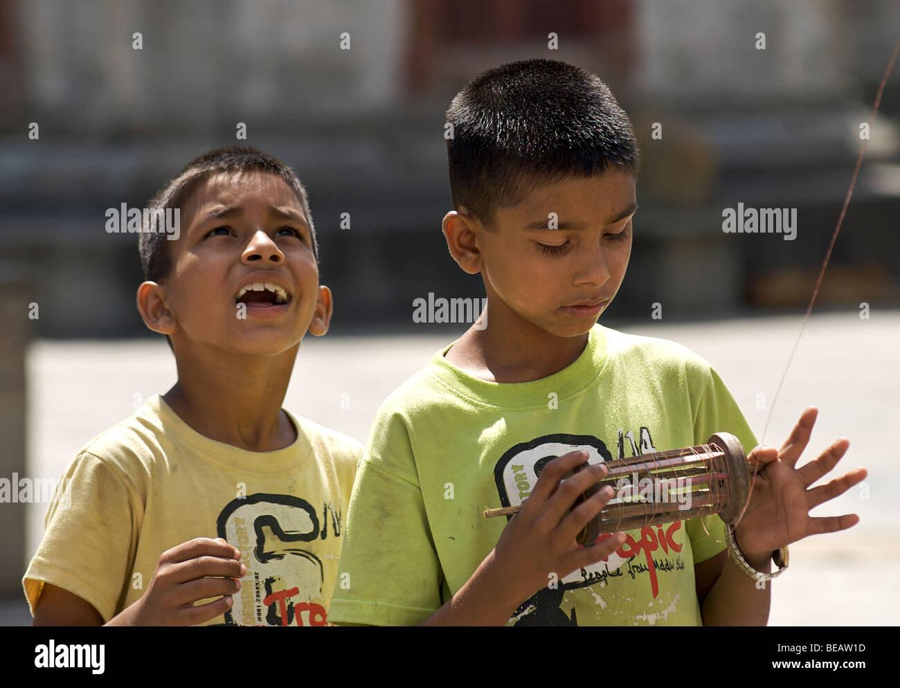 Nepalese boys kite flying with kite reel  in hand, Kathmandhu, Nepal - Stock Image