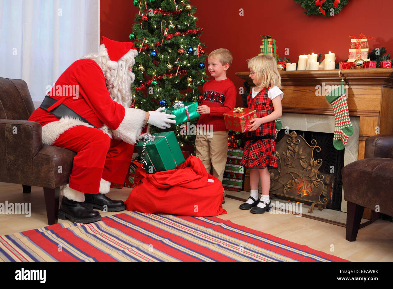 Santa Claus gives Christmas gifts to children - Stock Image