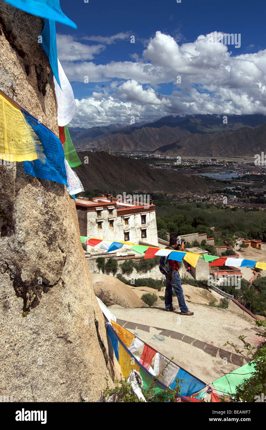 Drepung Monastery with Lhasa beyond, Tibet. Photographer pointing his camera towards Lhasa. Model Released subject - Stock Image