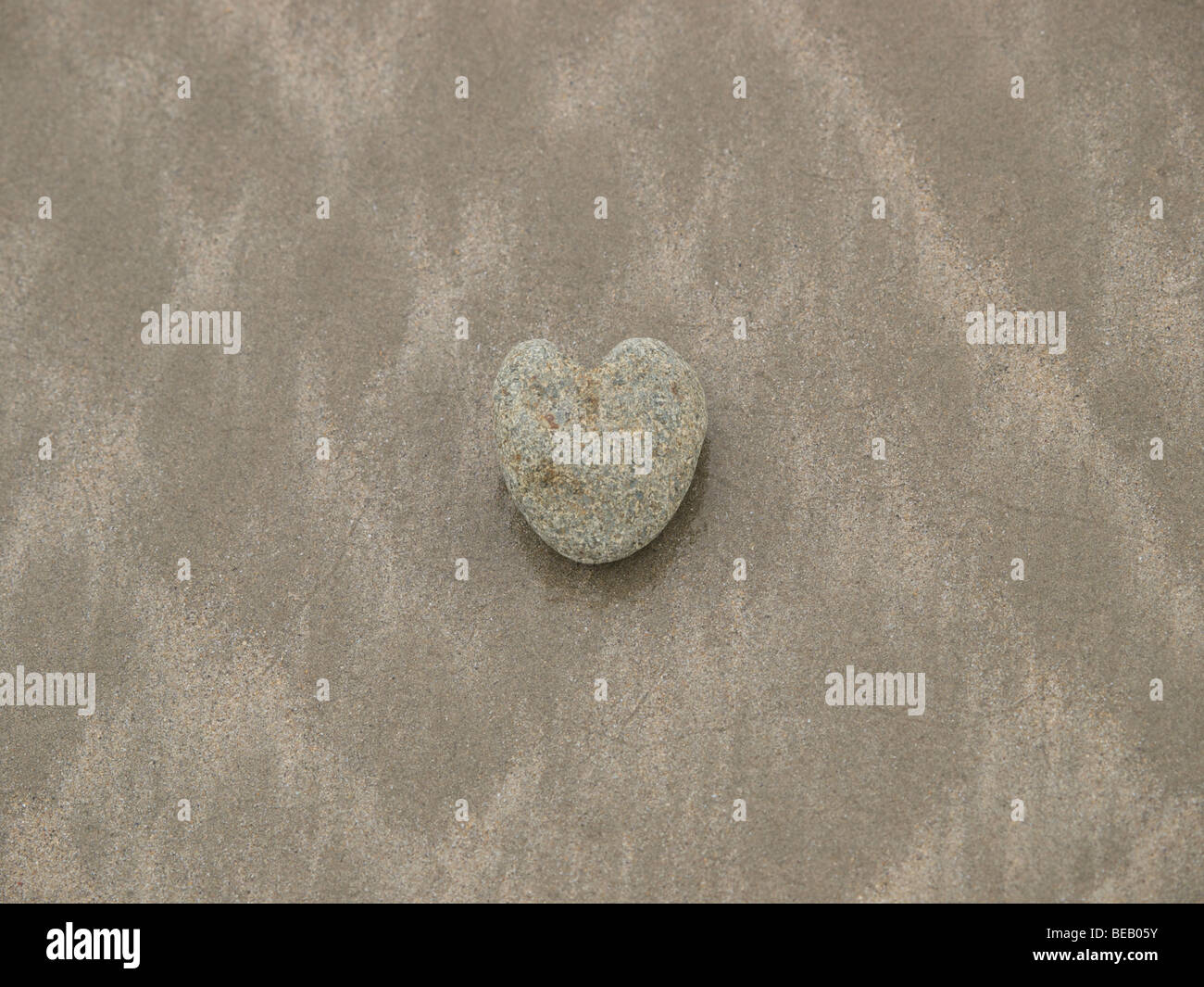 Heart of stone on a wet beach - Stock Image