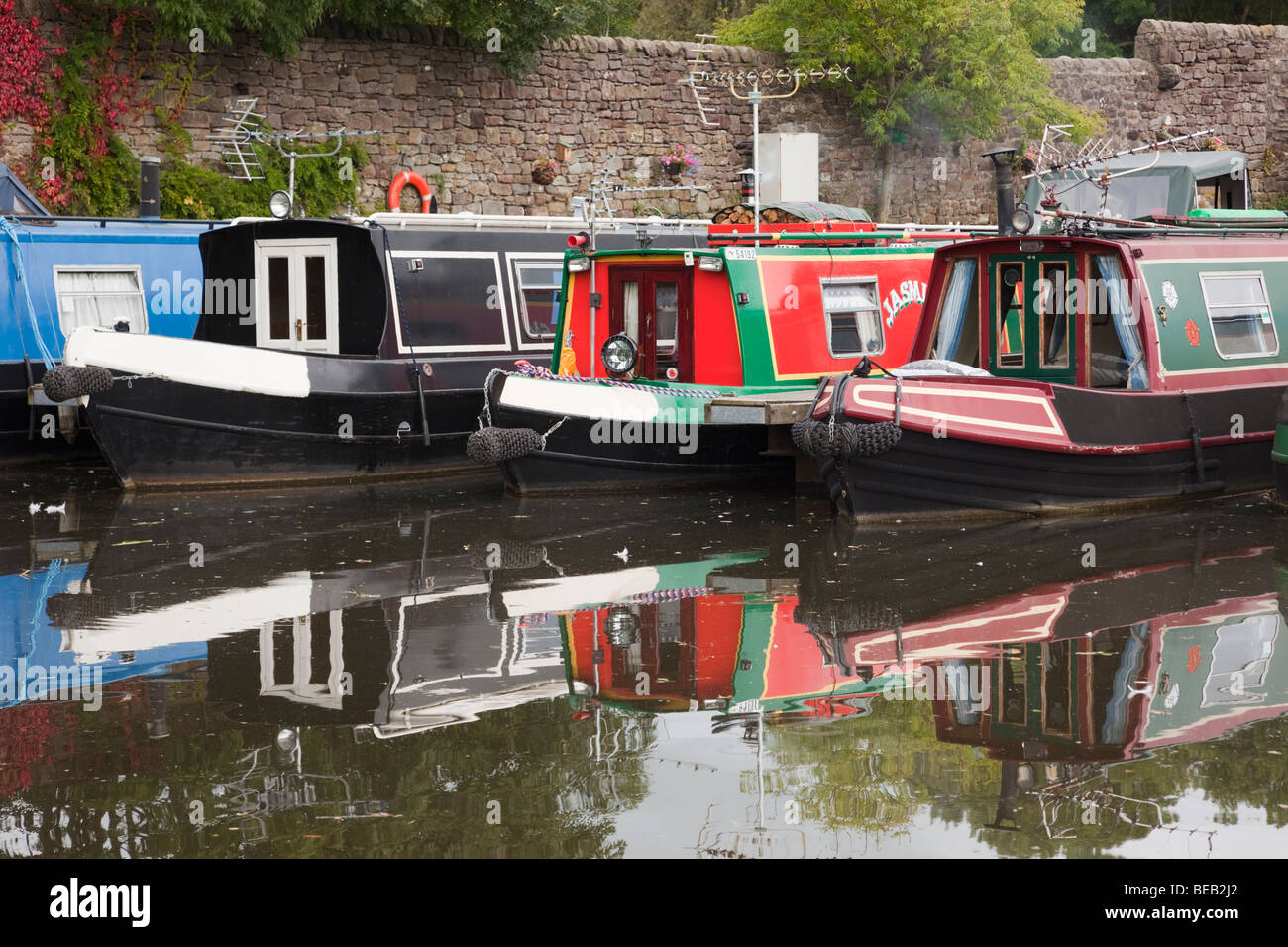 Galgate, Lancashire, England, UK, Europe. Moored narrowboats reflected in the water of the Lancaster canal basin. - Stock Image