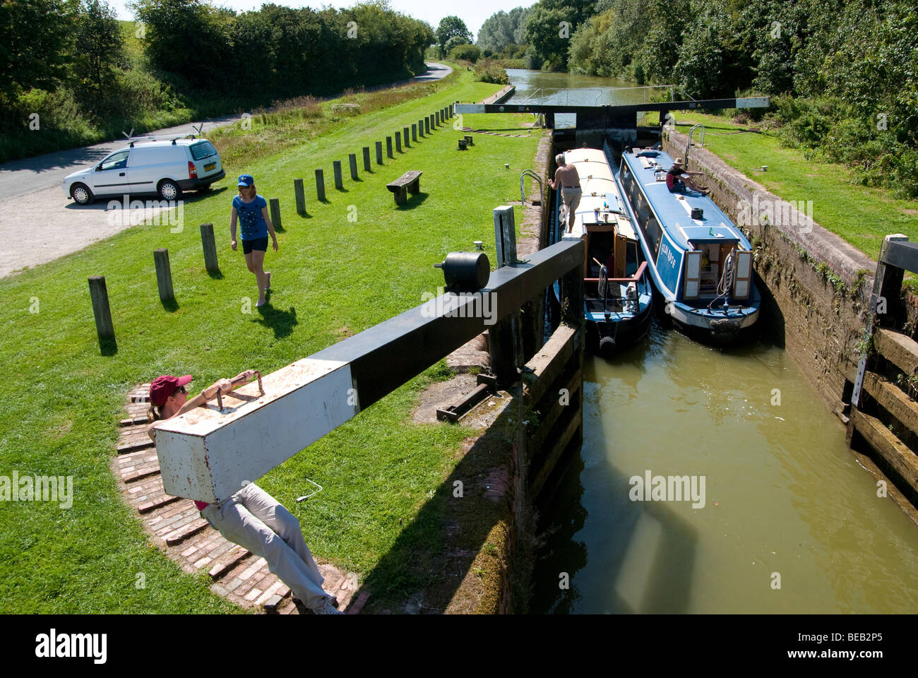 One girl pulling lock gate closed as two narrow boats going through lock 68 together west of Hungerford - Stock Image