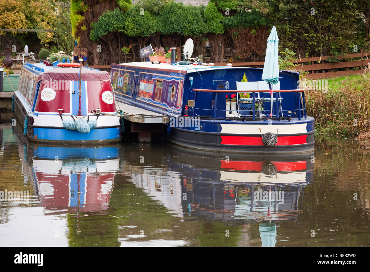 Galgate, Lancashire, England, UK. Two moored narrowboats reflected water in the Lancaster canal basin - Stock Image