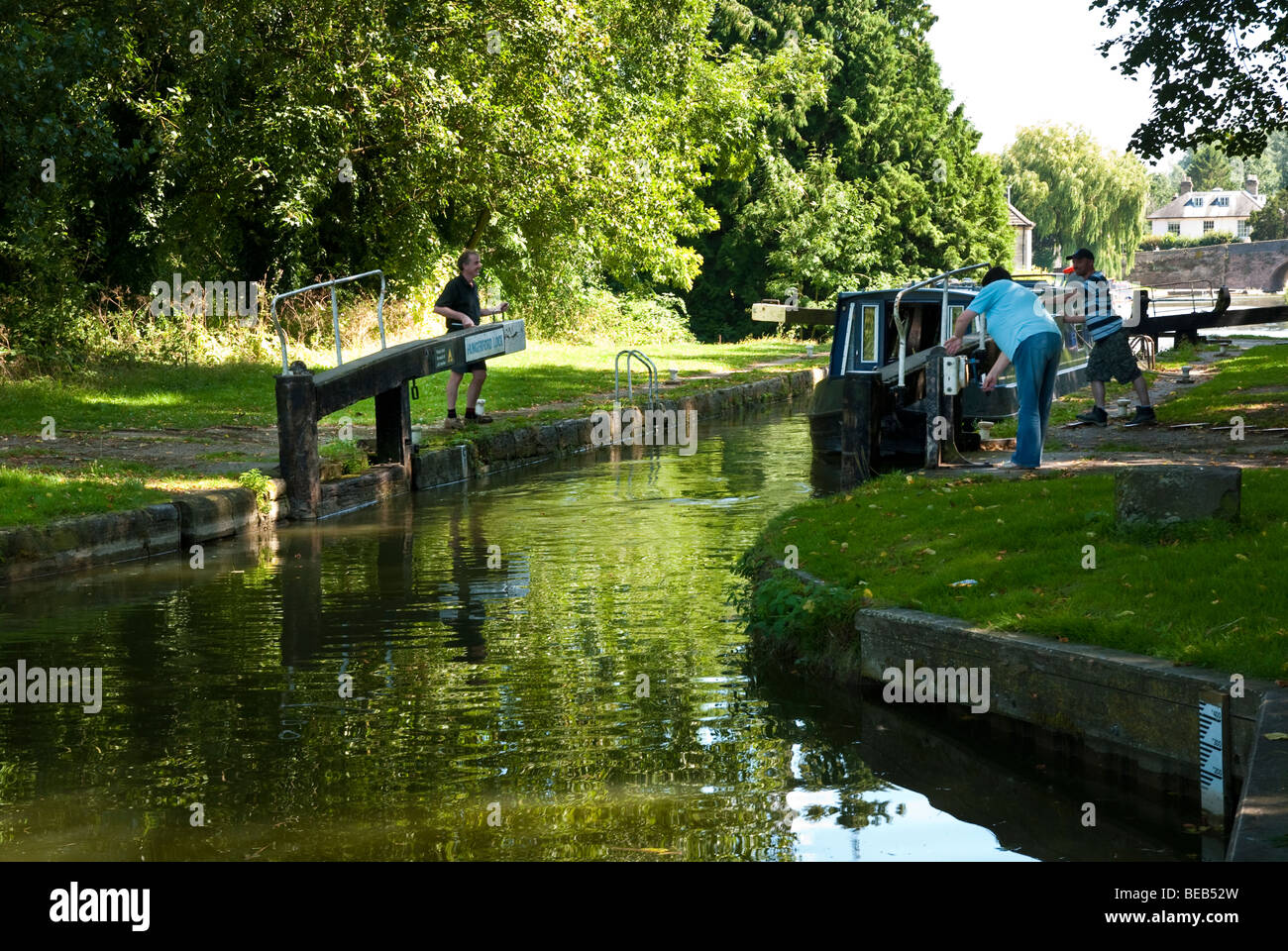 Man and woman opening lock gate for Narrow Boat  at Hungerford on the Kennet and Avon Canal - Stock Image