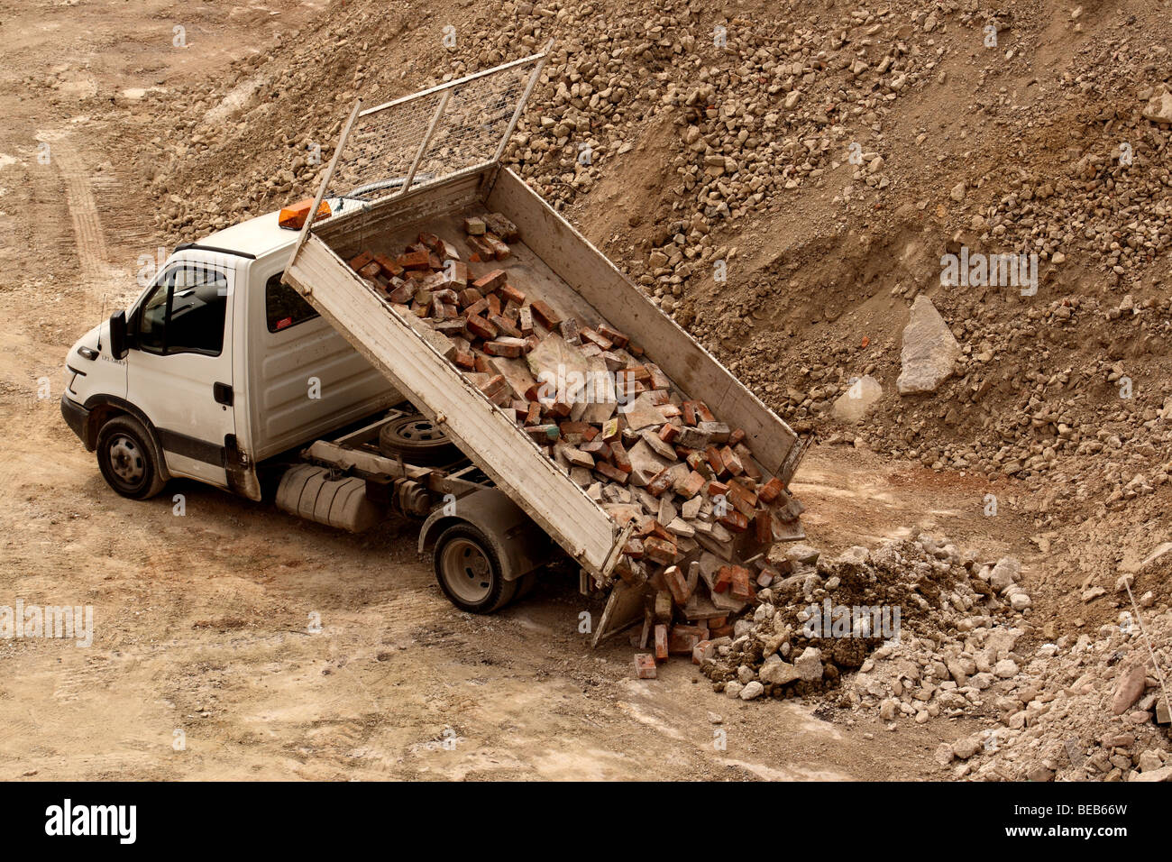 Small truck dumping a load of used bricks - Stock Image