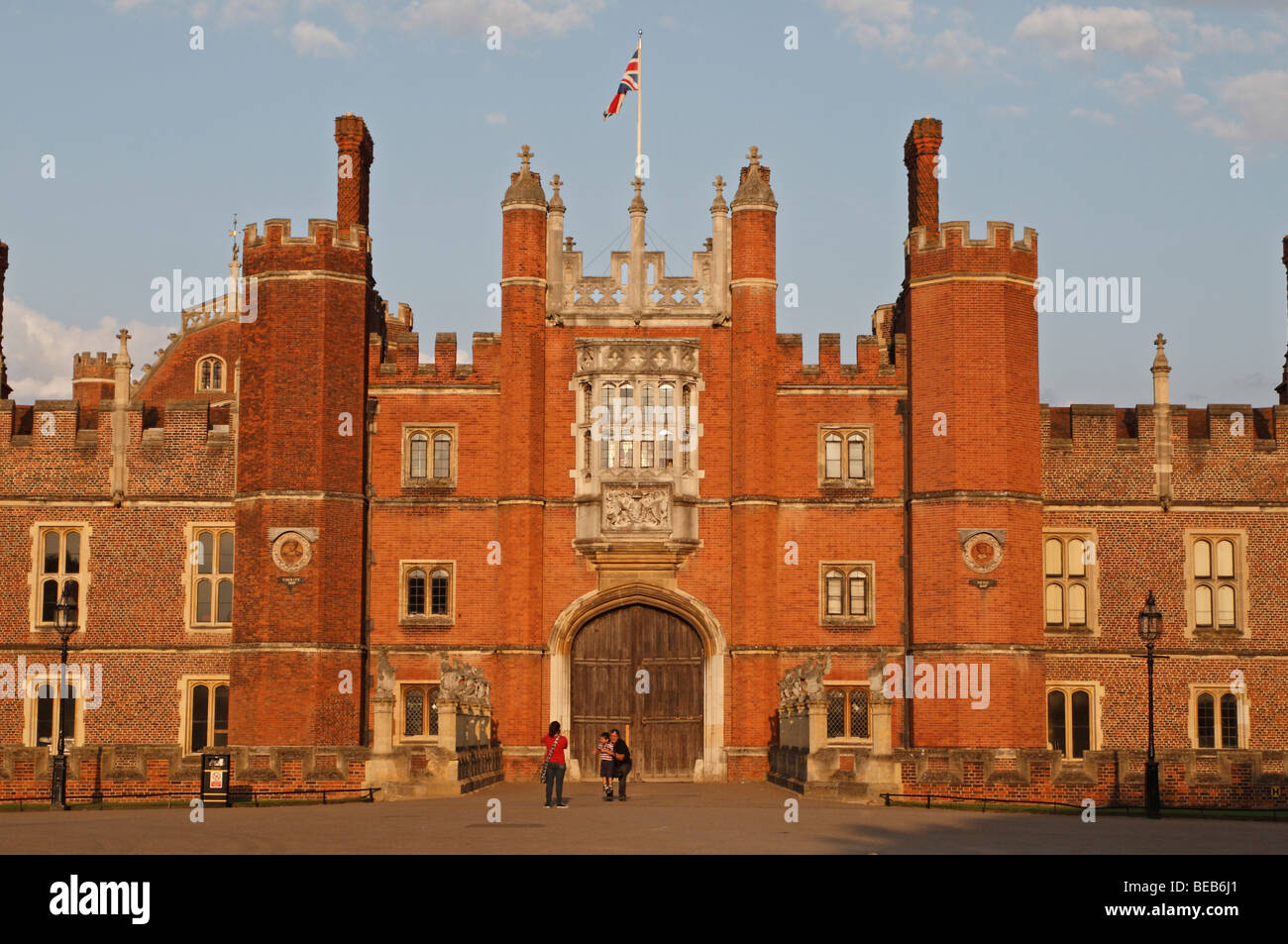 A mother photographs her family in front of the main entrance to Hampton Court Palace, Surrey, UK on a lovely summer's - Stock Image