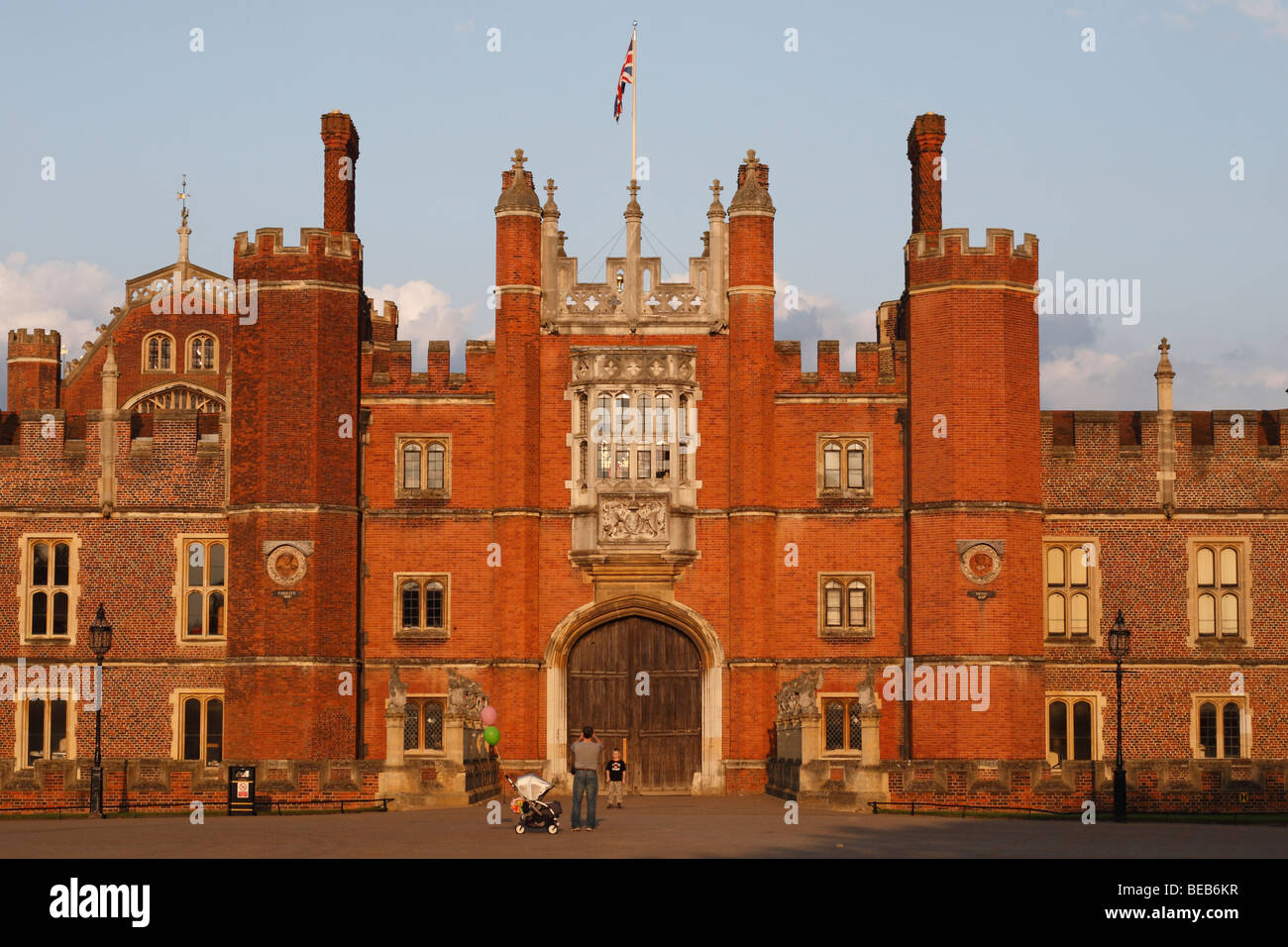 A father photographs his son in front of the main entrance to Hampton Court Palace, Surrey, UK on a lovely summer's - Stock Image