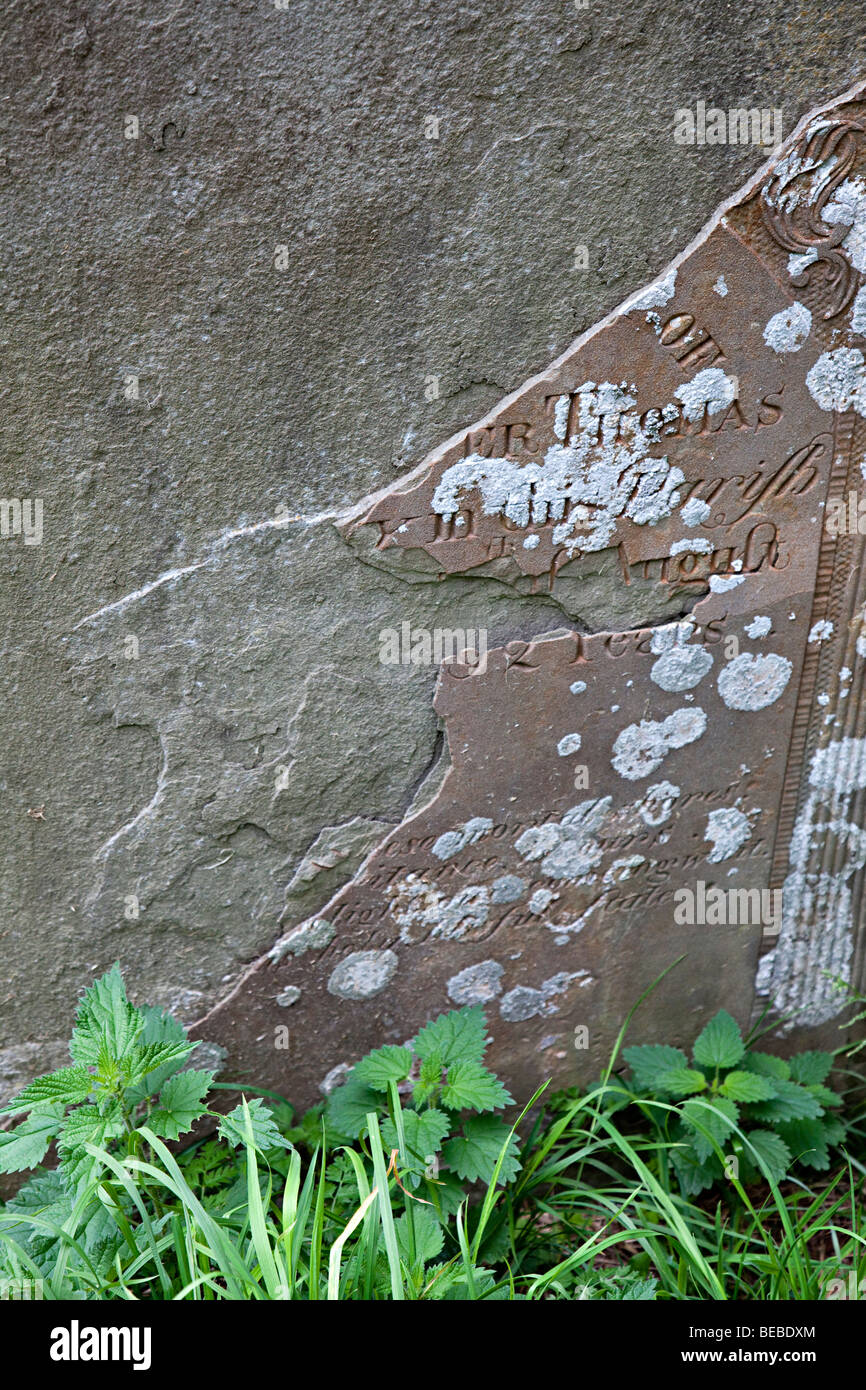 Gravestone weathered and flaking with lost inscription Wales UK - Stock Image