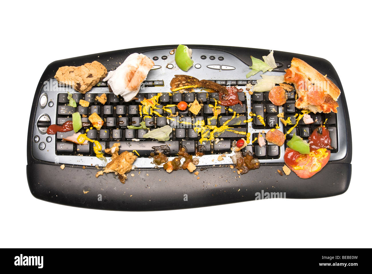 A keyboard covered with food remnants. - Stock Image