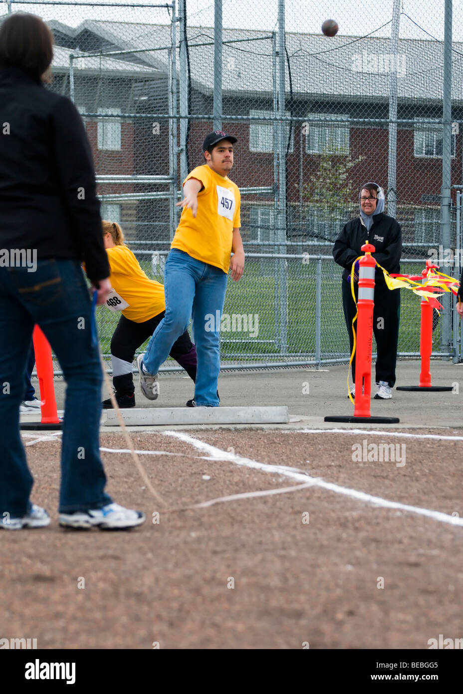A young man throws a shot put during competition at the Special Olympics in Tacoma, Washington. - Stock Image