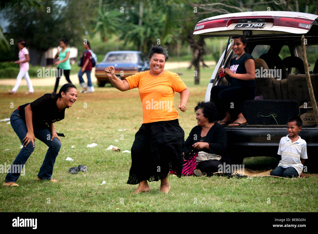 Tongan women brake into an impromtu dance after their team scores a try during a Saturday rugby match. - Stock Image