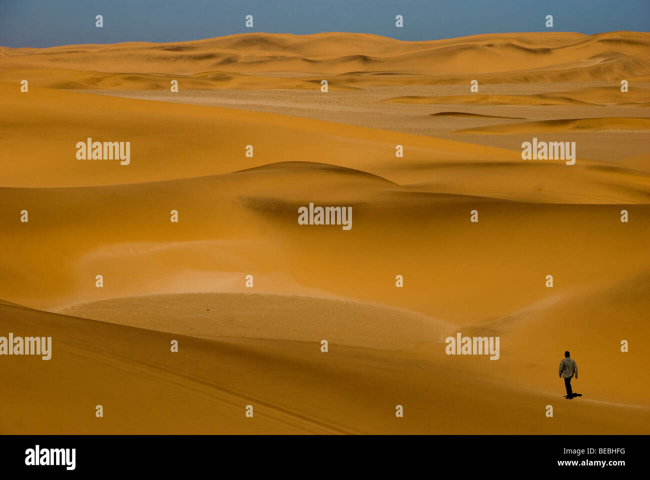 Tourist in desert dunes near Swakopmund, Namib Naukluft National Park, Namibia - Stock Image