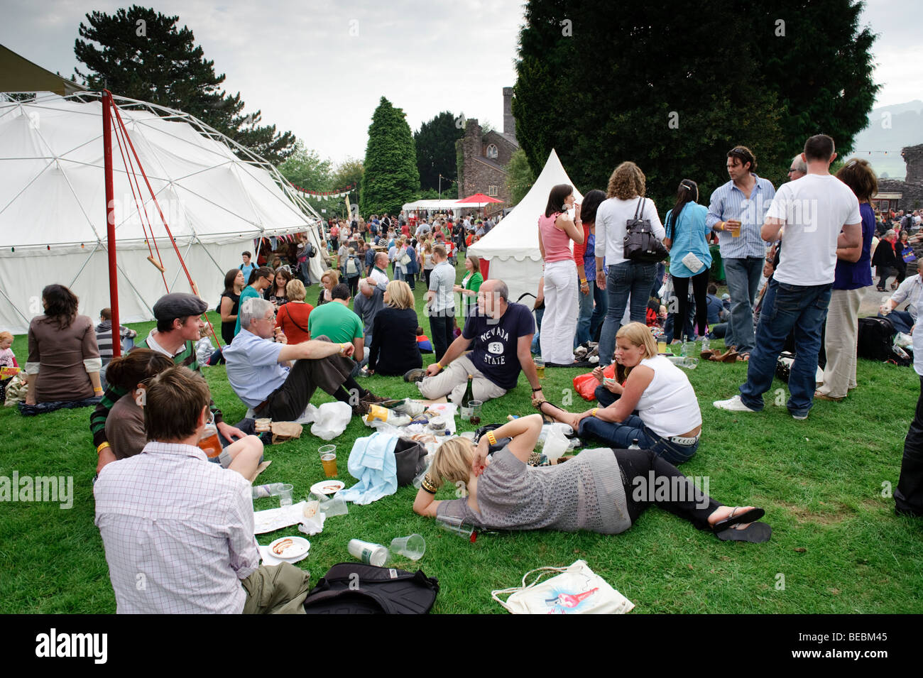 People relaxing in the castle grounds at the 2009 Abergavenny food festival, Monmouthshire south wales UK. - Stock Image