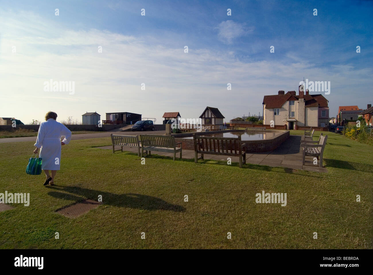 Woman wearing white dressing gown ready for bathing in the sea walking towards the beach in Aldeburgh - Stock Image
