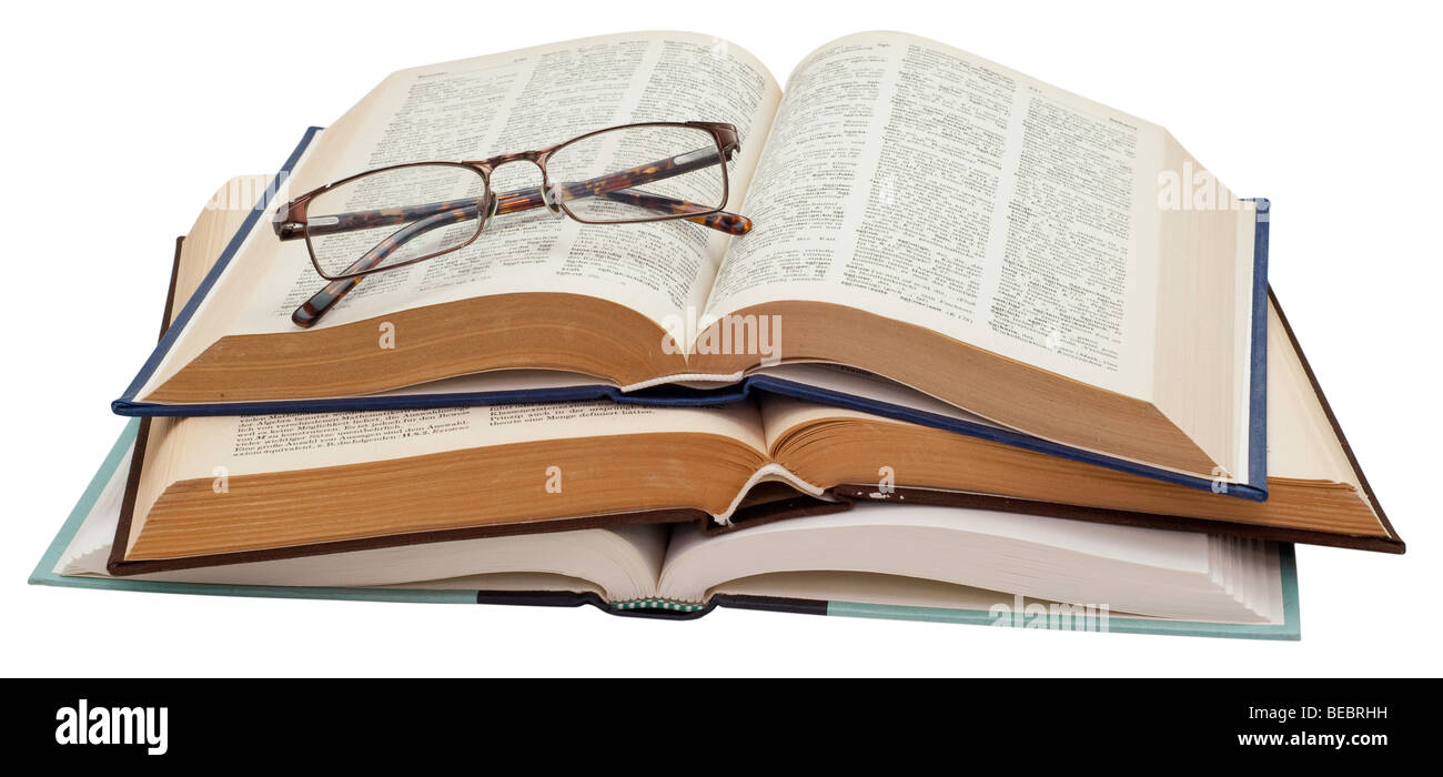Folded glasses on a stack three open books on white background, saved with clipping path - Stock Image