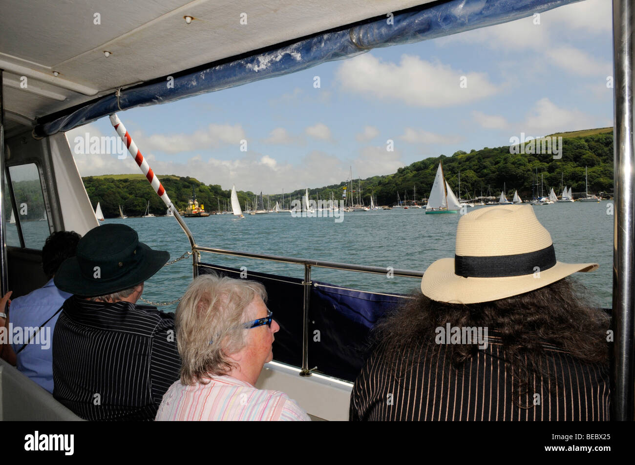 Passengers look onto sailing lessons out of the Fowey Ferry boat ride from Mevagissey to Fowey on a blue sky, sunny - Stock Image