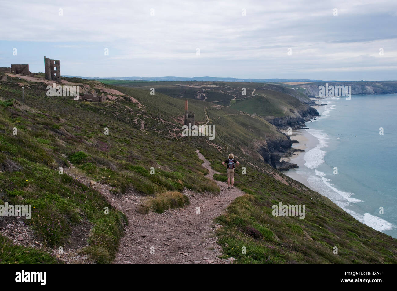Female walker strides along the Cornish coastal path towards the engine houses and tin mines of St Agnes, Cornwall. - Stock Image