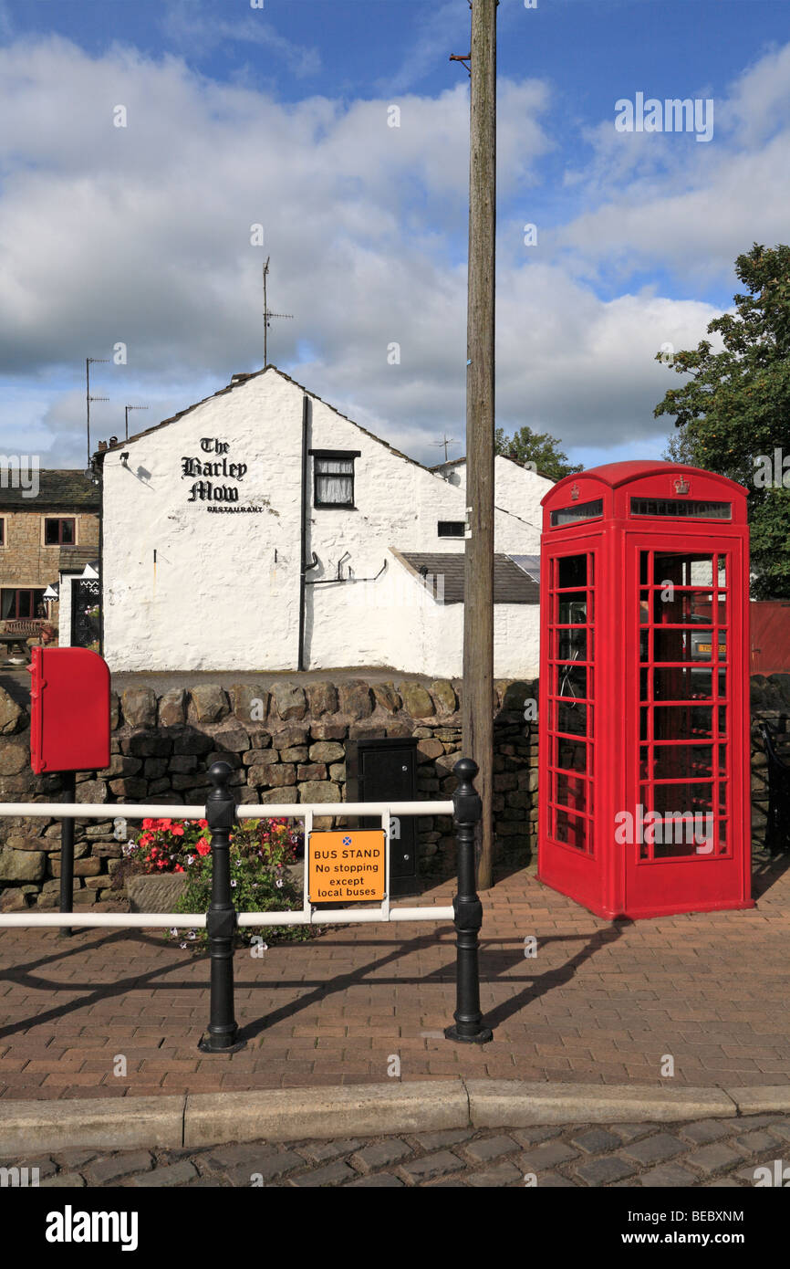 Red post box and telephone kiosk and the Barley Mow restaurant, Barley, Pendle, Lancashire, England, UK. - Stock Image
