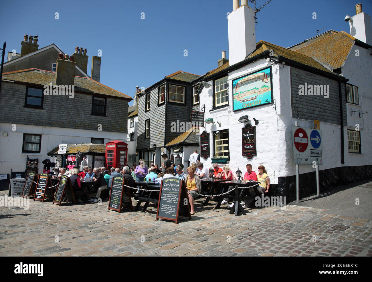 People eating and drinking outside The Sloop Inn pub on the sea front at St. Ives, Cornwall, England - Stock Image