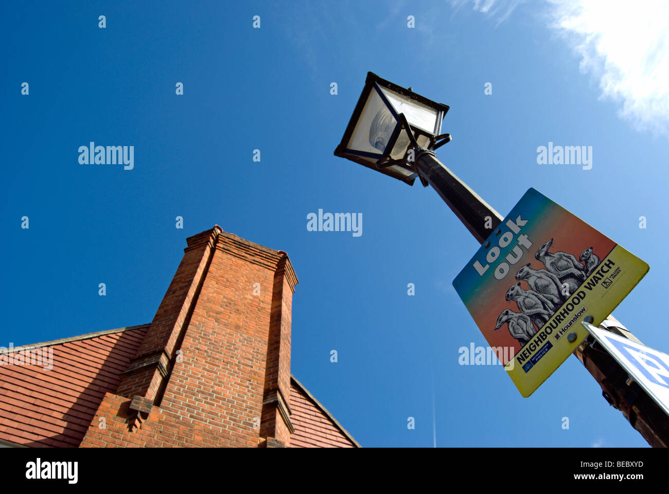 victorian style street lamp with neighbourhood watch sign and tall brick chimney, in bedford park, chiswick, england - Stock Image