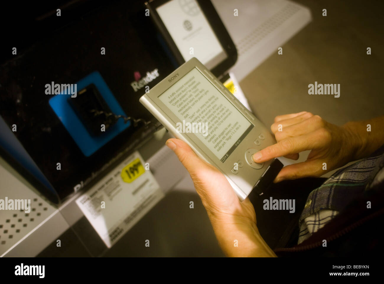 A customer at a Best Buy electronics store in New York examines a Sony Reader Pocket Edition ebook reader - Stock Image