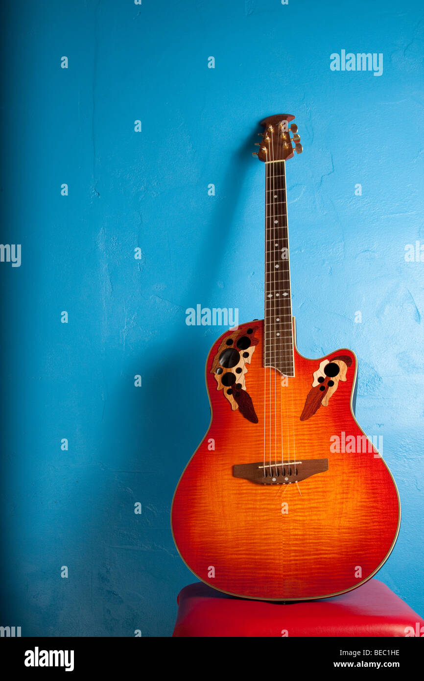 Simple semi-acoustic guitar against blue - Stock Image