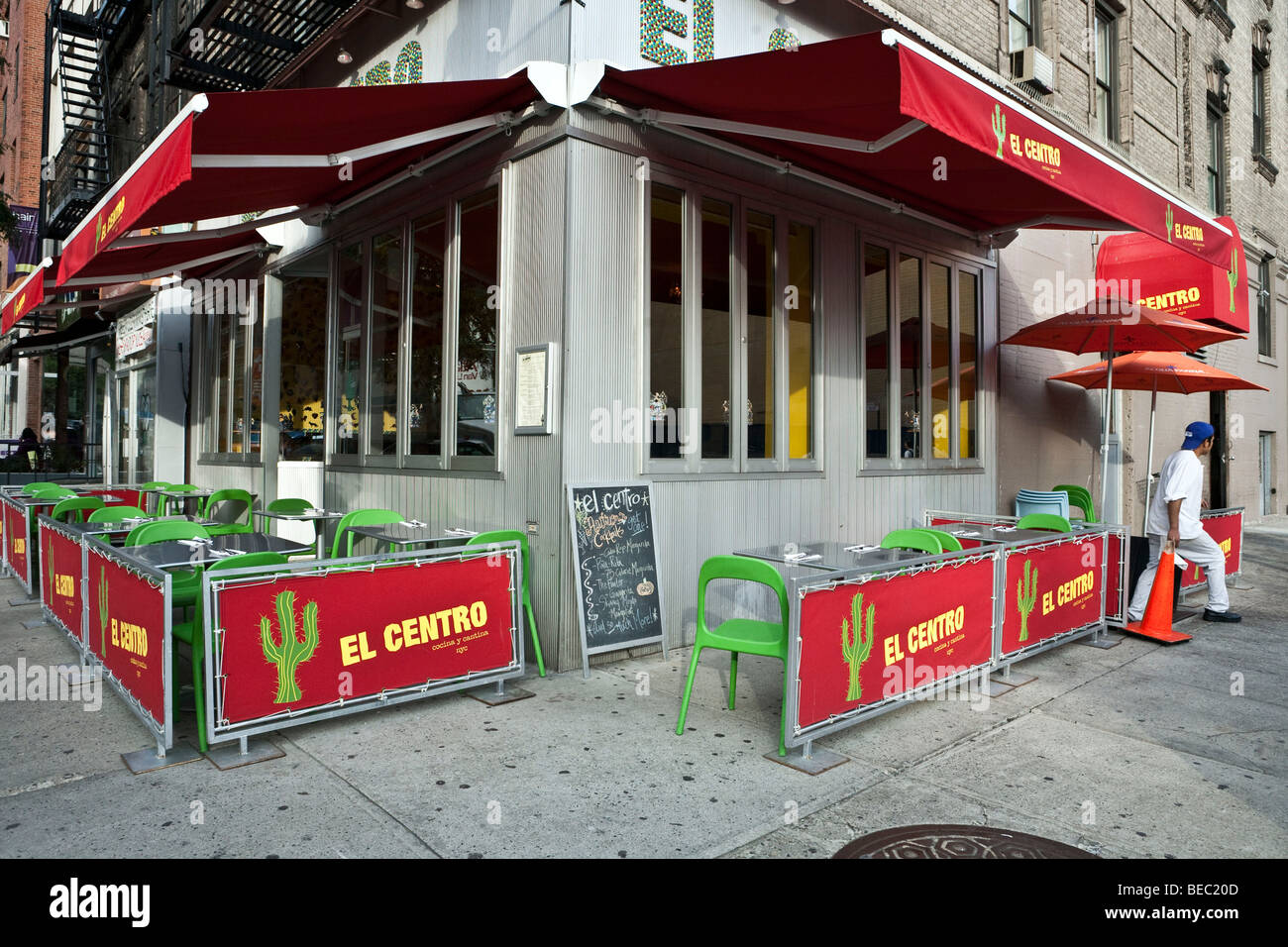 corner Mexican restaurant with awning & sidewalk seating in Mexican colors in New York City Hells Kitchen neighborhood - Stock Image