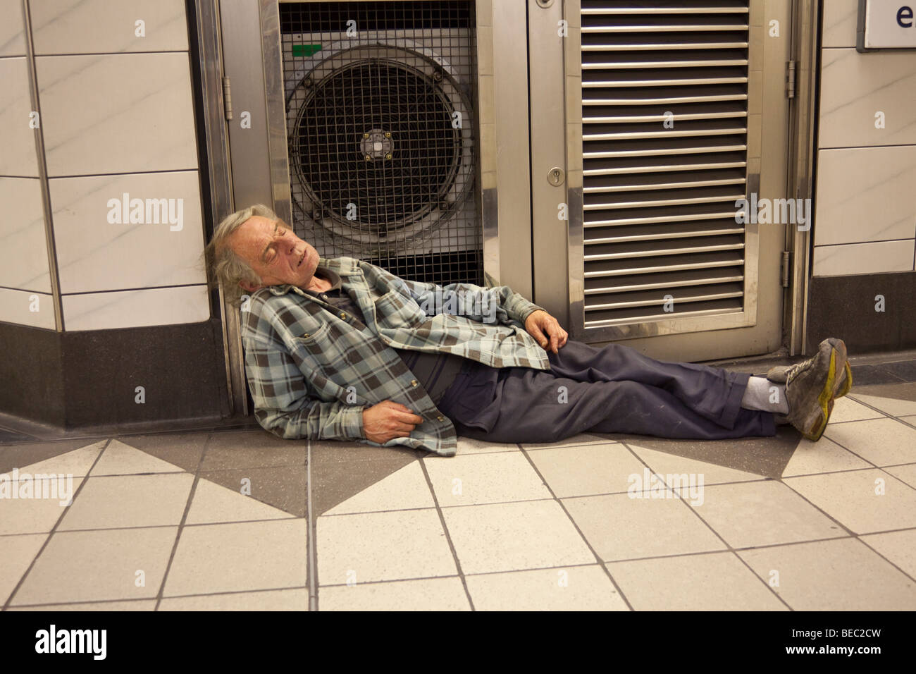 man asleep in London Bank underground station at night - Stock Image