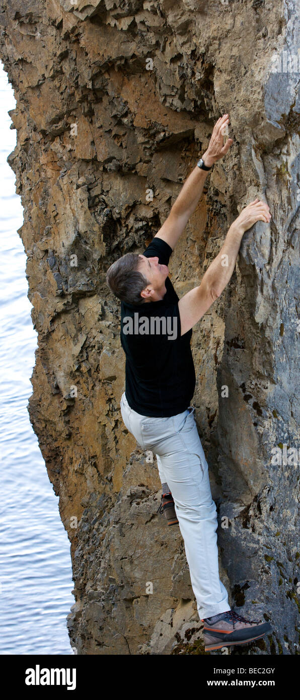a handsome middle aged man climbing a rock wall reaching for something to hold - Stock Image