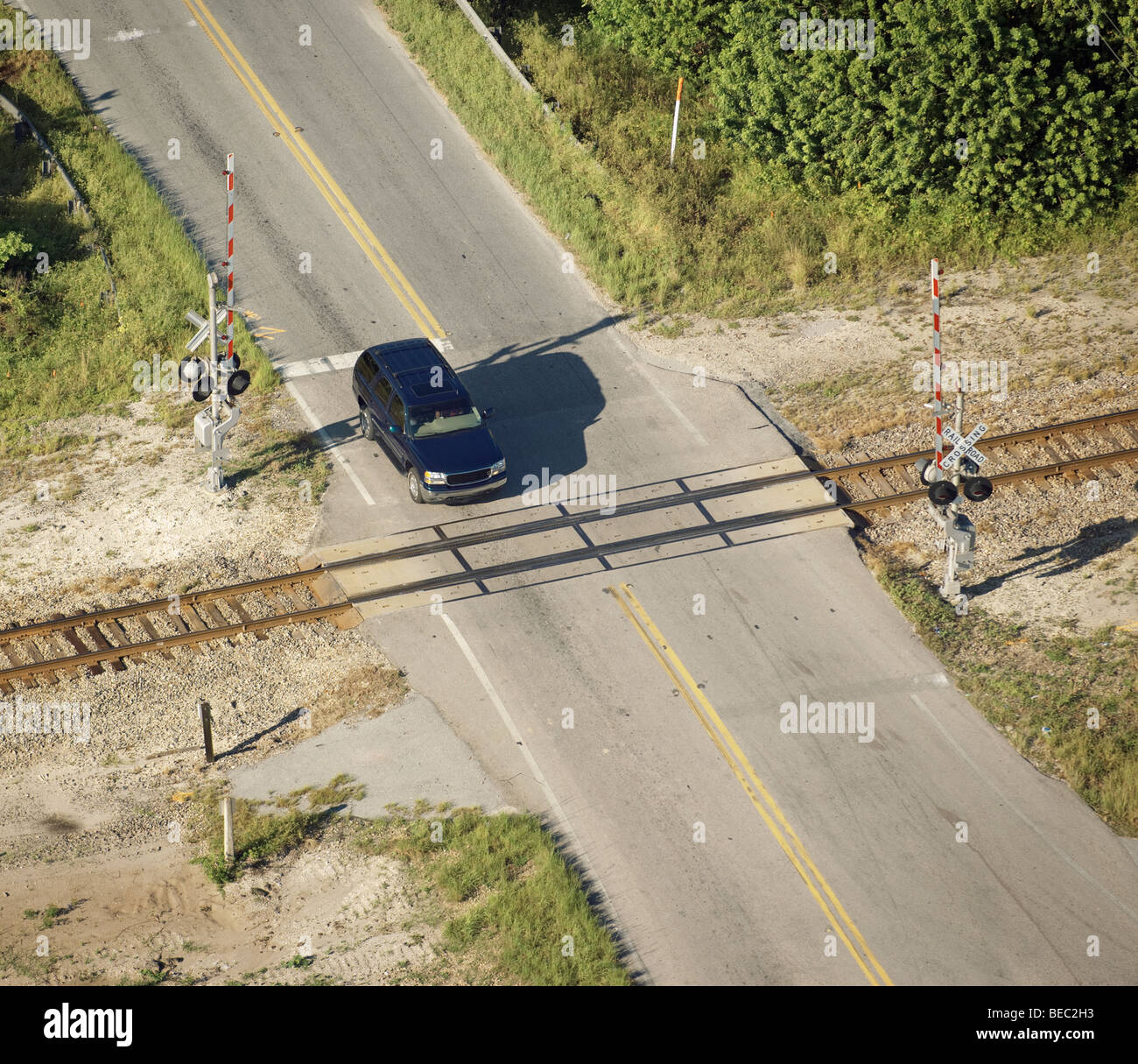 SUV going over a rural railroad crossing - Stock Image